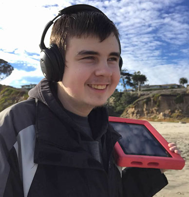 A student at the beach carrying an AAC device